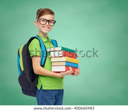 childhood, education and people concept - happy smiling student boy in eyeglasses with school bag and books over green school chalk board background - stock photo