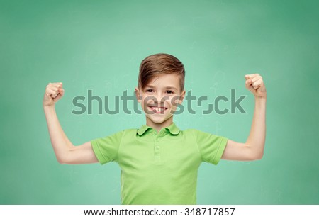 childhood, education, power, strength and people concept - happy smiling boy in green polo t-shirt showing strong fists over green school chalk board background - stock photo