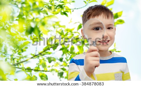 childhood, environment, ecology, discovery and people concept - happy little boy looking through magnifying glass over green natural background - stock photo
