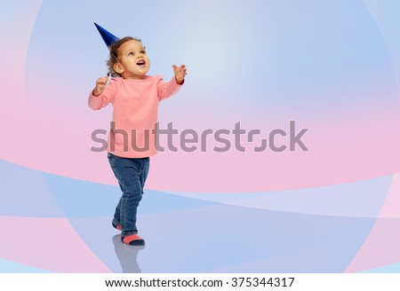 childhood, fashion, birthday, holidays and people concept - happy smiling african american little baby girl with birthday party hat playing and catching something over pink and violet background - stock photo