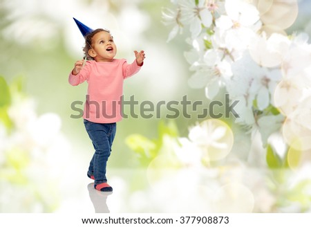 childhood, fashion, birthday, holidays and people concept - happy smiling african american little baby girl with birthday party hat playing and catching something over cherry blossoms background - stock photo