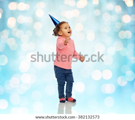 childhood, fashion, birthday, holidays and people concept - happy smiling african american little baby girl with birthday party hat looking up at something over blue holidays lights background - stock photo