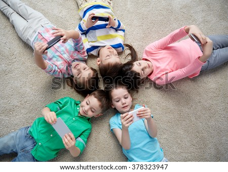 childhood, fashion, friendship and people concept - group of happy smiling little children with smartphones lying on floor - stock photo