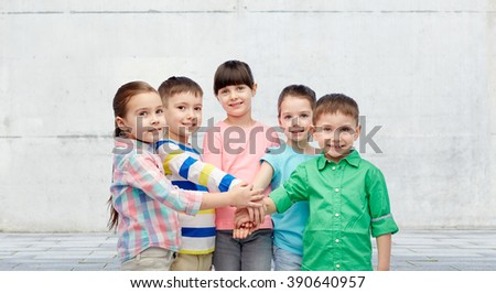 childhood, fashion, friendship and people concept - happy little children with hands on top over concrete wall on street background - stock photo