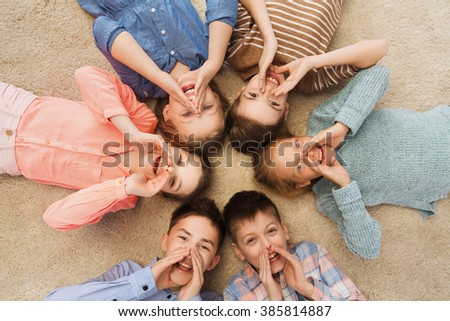 childhood, fashion, friendship and people concept - happy smiling children lying on floor in circle and calling or shouting - stock photo