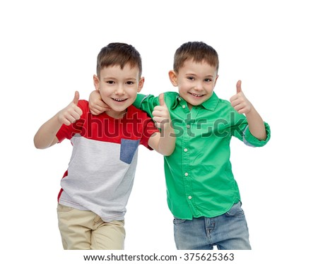 childhood, fashion, friendship and people concept - happy smiling little boys showing thumbs up - stock photo
