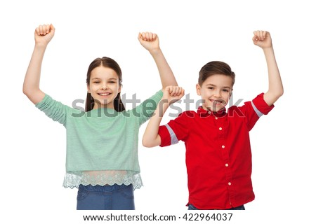 childhood, fashion, gesture and people concept - happy smiling boy and girl raising fists and celebrating victory - stock photo