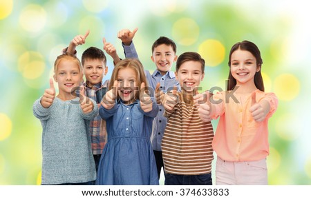 childhood, fashion, gesture and people concept - happy smiling children showing thumbs up over green lights background - stock photo