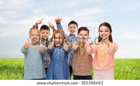 childhood, fashion, summer, gesture and people concept - happy smiling children showing thumbs up over blue sky and grass background - stock photo