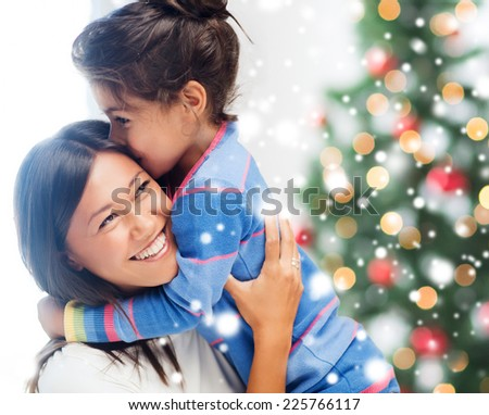 childhood, happiness, christmas, family and people concept - smiling little girl and mother hugging indoors - stock photo