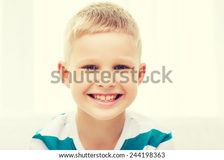 childhood, happiness, home and people concept - portrait of smiling little student boy at home - stock photo