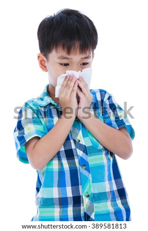 Childhood, health care and medicine concept. Handsome asian boy blowing his nose into tissue paper. - stock photo