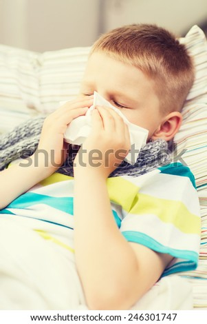 childhood, healthcare and medicine concept - ill boy with flu at home - stock photo