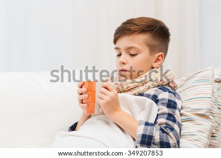 childhood, healthcare, people and medicine concept - ill boy with flu lying in bed and drinking tea at home - stock photo