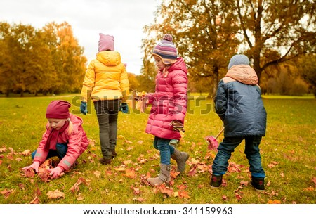 childhood, leisure, autumn, friendship and people concept - group of children with rack collecting and racking leaves in park - stock photo