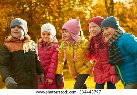 childhood, leisure, friendship and people concept - group of happy kids playing game and having fun in autumn park - stock photo