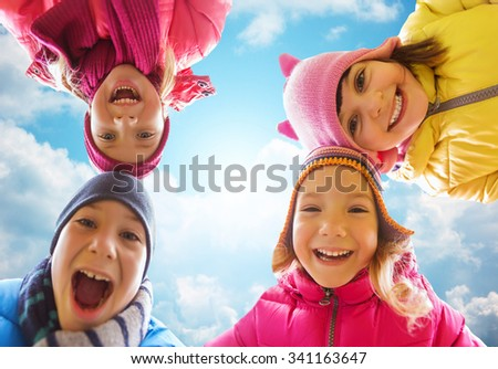 childhood, leisure, friendship and people concept - happy little children faces outdoors over blue sky and clouds background - stock photo