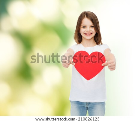 childhood, love, charity, ecology and people concept - smiling little girl sitting and holding red heart cutout over green background - stock photo