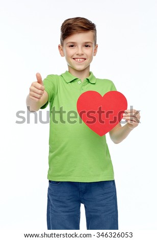 childhood, love, charity, health care and people concept - happy smiling boy in green polo t-shirt holding blank red heart shape and showing thumbs up - stock photo