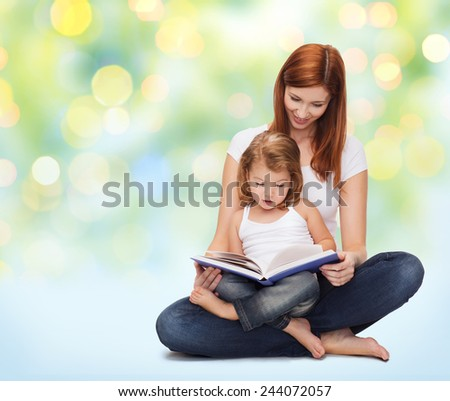 childhood, parenting and literature concept - happy mother with adorable little girl reading book over green lights background - stock photo