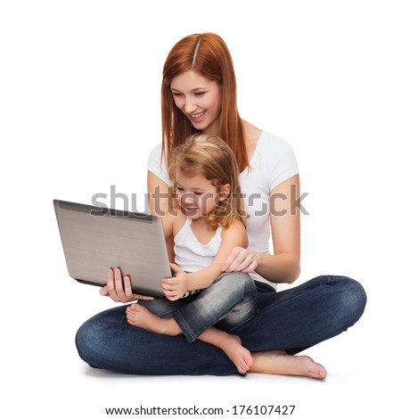 childhood, parenting and technology concept - happy mother with adorable little girl with laptop - stock photo