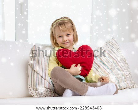 childhood, people, holidays and happiness concept - smiling little girl with big red heart shaped pillow sitting on sofa at home - stock photo