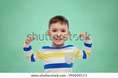 childhood, power, education, gesture and people concept - happy smiling little boy with raised hand over green school chalk board background - stock photo