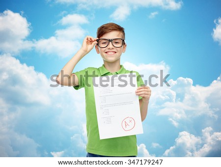 childhood, school, education and people concept - happy smiling boy in eyeglasses holding paper with test result over blue sky and clouds background - stock photo