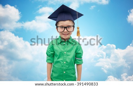 childhood, school, education, learning and people concept - happy boy in bachelor hat or mortarboard over blue sky and clouds background - stock photo