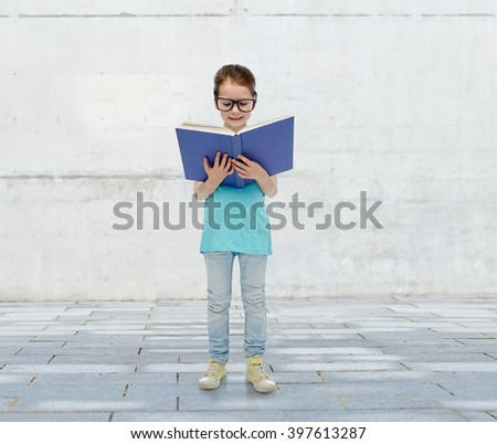 childhood, school, education, vision and people concept - happy little girl in eyeglasses reading book over urban concrete background - stock photo