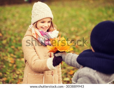 childhood, season and people concept - smiling little girl and boy with autumn leaves in park - stock photo