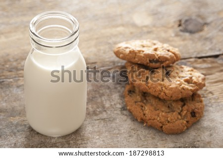 Childhood treat of a glass bottle of fresh milk served with crunchy cookies for a delicious snack - stock photo