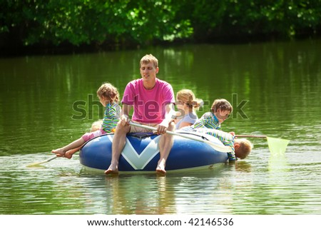 Children and adults float on an inflatable boat in a sunny day - stock photo