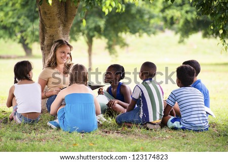 Children and education, young woman at work as educator reading book to boys and girls in park - stock photo