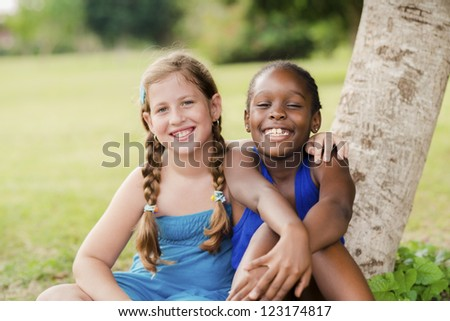 Children and friendship, portrait of two young girls hugging, smiling and looking at camera while sitting near tree in park - stock photo
