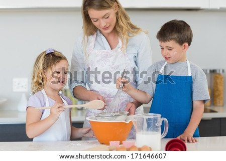 Children and mother baking cookies at counter top in kitchen - stock photo