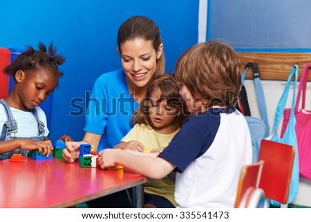 Children and nursery teacher building with blocks in kindergarten - stock photo