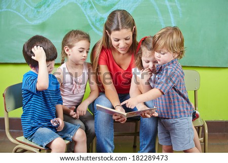 Children and nursery teacher reading book together in kindergarten - stock photo
