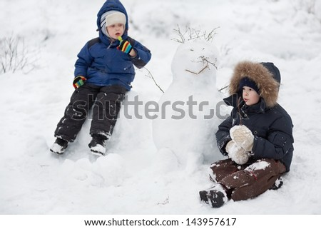 Children and snowman/Two boys sitting in the snow. Nearby is a snowman. Winter - stock photo