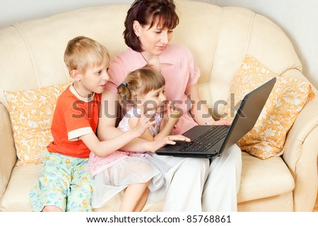 Children and their mother using a computer at home - stock photo