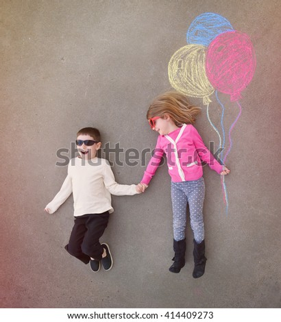 Children are holding hands outside with colorful chalk balloons sketched out on cement for a creative, craft or play concept. - stock photo