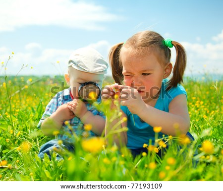 Children are playing on green meadow examining field flowers using magnifying glass - stock photo