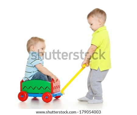 Children are playing with toy handcart on a white background. One little boy sits in handcart, another child pulls him. Merry riding. - stock photo