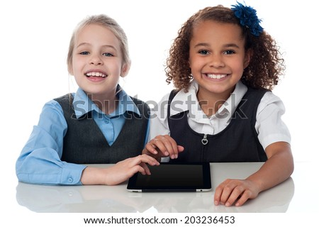 Children are using tablet while sitting at table - stock photo