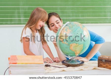 Children at school - teacher showing globe - stock photo