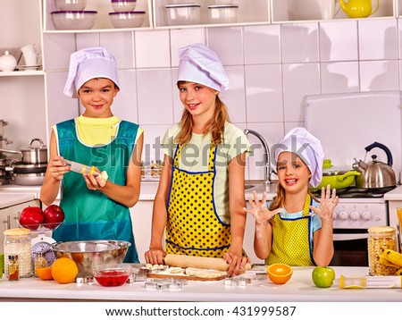 Children bake cookies at kitchen. Children cookies bake something from dough on home kitchen. - stock photo