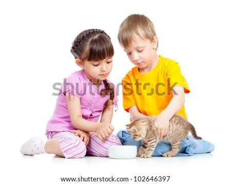 children boy and girl feeding attractive kitten - stock photo