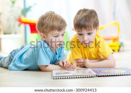 Children boys play together lying on floor - stock photo