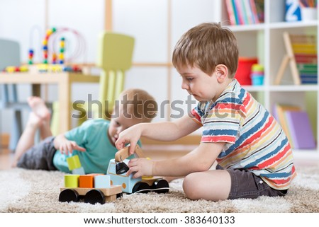 children boys toddlers playing with toy car indoors - stock photo