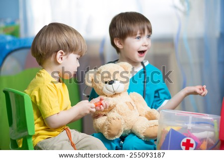 children brothers play doctor with plush toy at home - stock photo